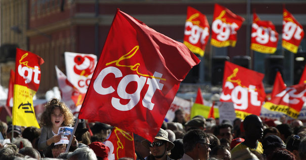 Private and public sector workers hold CGT union flags as they attend a demonstration over pension reforms in Nice
